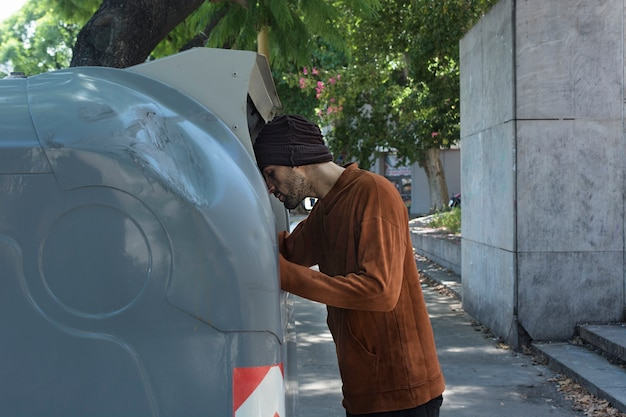 Sans-abri regardant à travers les poubelles dans les rues
