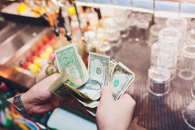Un sans-abri tient un billet en dollars dans sa main. mise au point sélective à la facture en dollars.