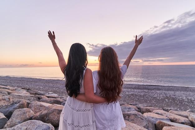 Sans insouciance fille heureuse et mère en robes blanches se tient ensemble sur une pierre à bras ouverts au bord de la mer au coucher du soleil en été