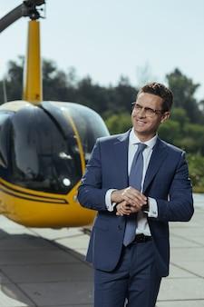 Sans perdre de temps. enthousiaste jeune homme d'affaires debout sur un héliport et en attente d'un pilote d'hélicoptère tout en vérifiant l'heure sur sa montre