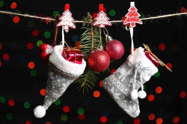 Santa chaussette, chapeau et accessoires de noël sur fond noir avec des lumières