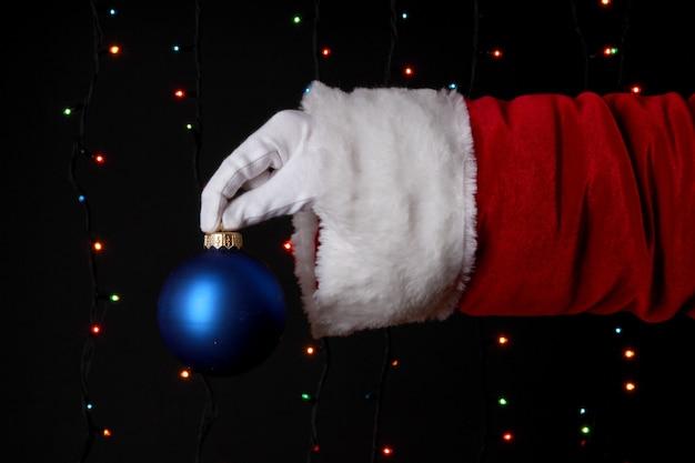 Santa claus hand holding christmas ball sur fond clair