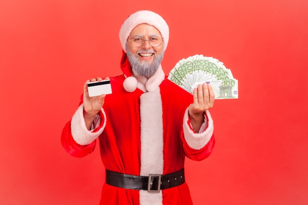 Santa claus holding montrant fan de billets en euros et carte de crédit en mains.