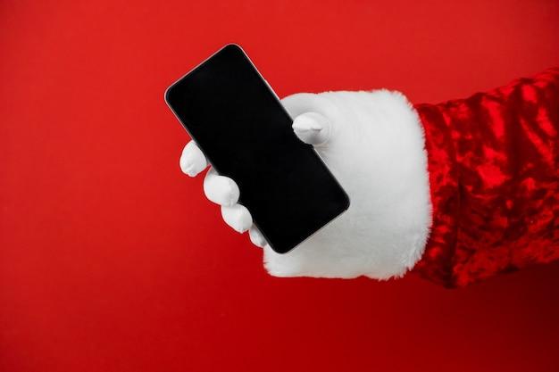 Santa claus main tenant un smartphone avec un écran vide.