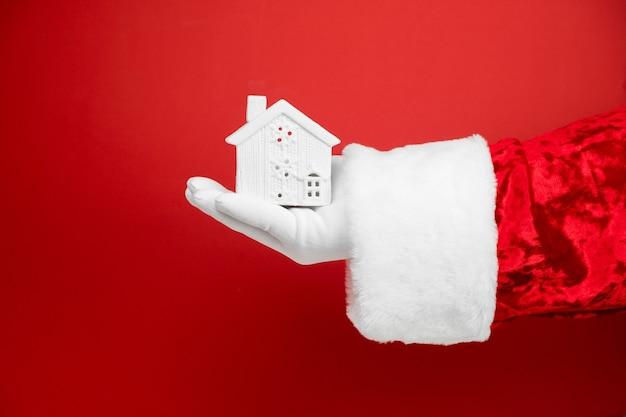 Santa main tient le cadeau de la maison.