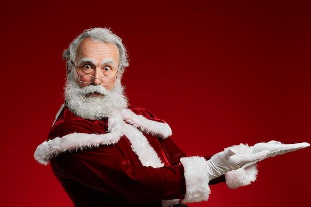 Santa pointant sur fond rouge
