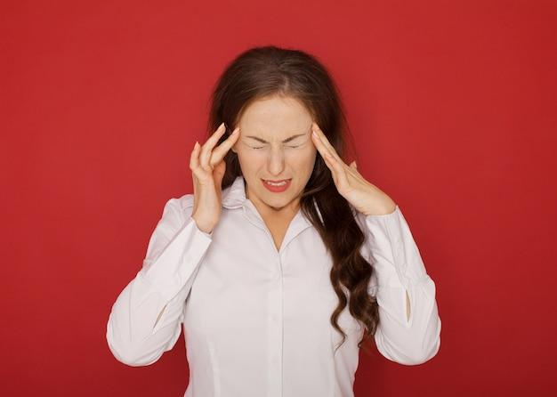 Santé et douleur. jeune femme épuisée stressée ayant de fortes céphalées de tension.