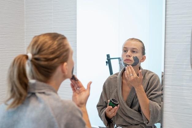 Santé des femmes. spa et bien-être. femme en peignoirs gris appliquant un masque facial dans la salle de bain en regardant le miroir