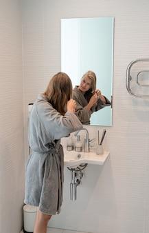 Santé des femmes. spa et bien-être. jeune femme en peignoirs gris se brosser les cheveux et souriant tout en regardant le miroir