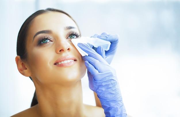 Santé. jeune femme appliquer des gouttes pour les yeux. vue fraîche. portrait d'une belle femme aux yeux verts.