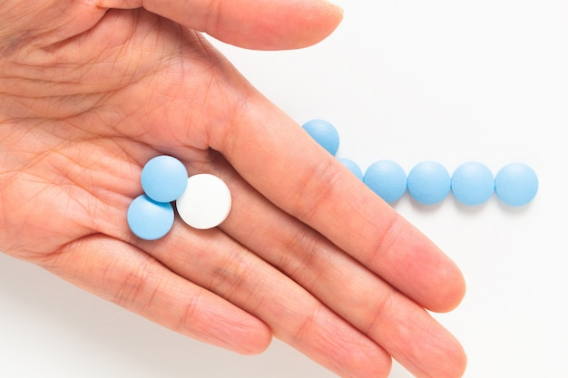 Santé et médicaments concept de pilules bleues et blanches de drogue ou de comprimés dans la main de la femme avec espace de copie