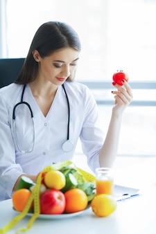 Santé. régime alimentaire et en bonne santé. docteur diététiste tenant une tomate fraîche