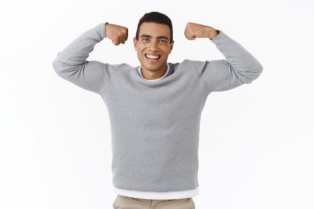 Santé et sport. heureux jeune homme athlétique souriant et souriant, flex biceps et riant, devenant fort