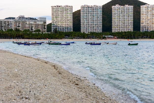 Sanya, hainan, chine - 20 février 2020: bateaux de pêche au coucher du soleil, mer turquoise claire avec récifs coralliens sur la côte de la baie de xiaodonghai en mer de chine méridionale. paysage naturel.