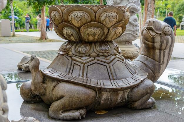 Sanya, hainan, chine - 20 février 2020: tortue en pierre à motifs avec baignoire et eau à l'arrière sur le territoire du centre bouddhiste nanshan.