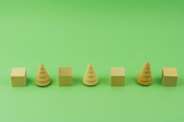 Sapin en bois. et cubes d'affilée sur fond vert. jouets écologiques. sauvez les forêts, concept de sensibilisation. investissements respectueux de l'environnement. la sciure de bois de l'industrie du bois. scierie, menuiserie