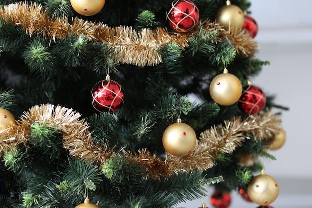Sapin de noël artificiel décoré de boules en or rouge et de guirlandes. concept de décoration de nouvel an