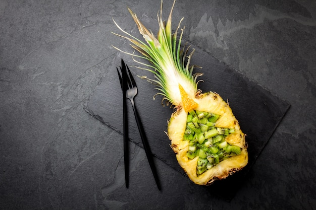 Sapin de noël à base d'ananas et de kiwi sur ardoise.