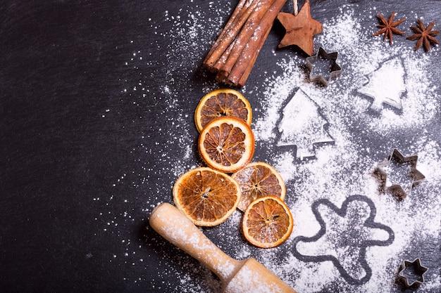 Sapin de noël à base de farine sur une table sombre ingrédients pour la cuisson et les fruits secs