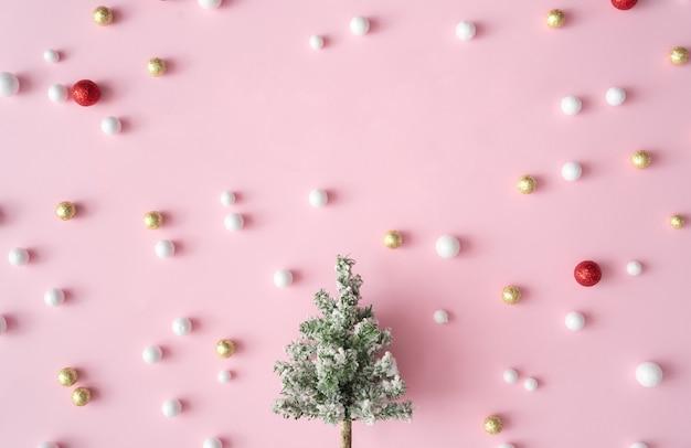 Sapin de noël avec boules de décoration de paillettes rouges, or et blanches. carte de voeux de fête du nouvel an fond rose avec espace de copie. style minimal. composition à plat.