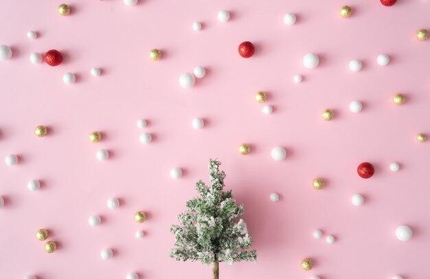 Sapin de noël avec boules de décoration de paillettes rouges, or et blanches. carte de voeux de fête de nouvel an fond rose. style minimal. composition à plat.