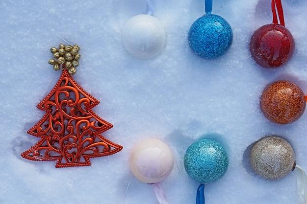 Sapin de noël et boules sur la neige.