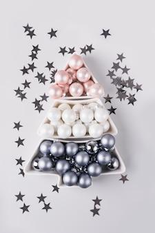 Sapin de noël en boules pastel argentées sur fond gris. composition de noël. mise à plat, vue de dessus, fond. carte de voeux de vacances.
