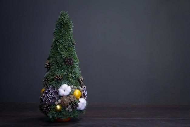 Sapin de noël en branches de sapin et décoré de matériaux naturels et de boules