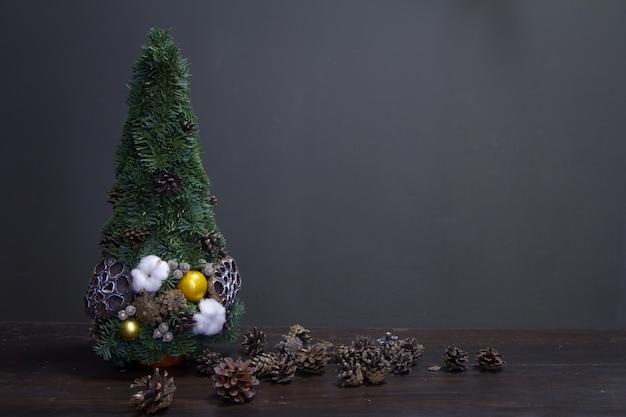 Sapin de noël en branches de sapin et décoré de matériaux naturels et de nombreux cônes