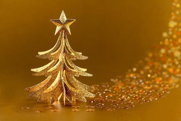 Sapin de noël brillant et confettis en forme d'étoiles scintillantes sur l'or