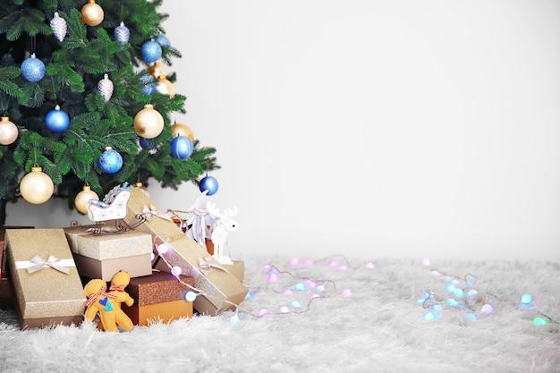 Sapin de noël avec des cadeaux sur le sol dans une chambre