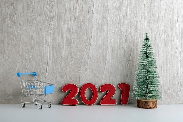 Sapin de noël, chariot et numéros 2021 sur fond clair. shopping pour la nouvelle année. copiez l'espace.