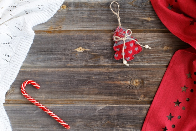 Sapin de noël avec coeurs, canne à sucre caramel, plaid en laine blanche et nappe rouge avec des étoiles sur une table en bois rustique