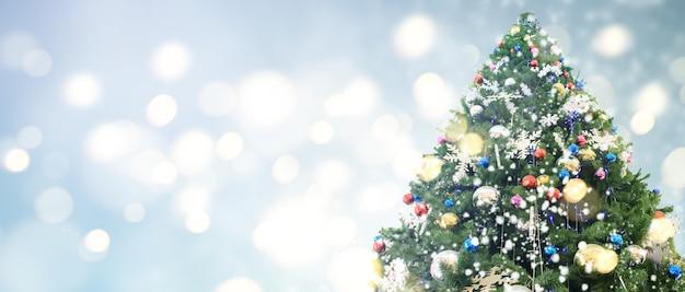 Sapin de noël décoré accroché à des branches de pin et des ornements