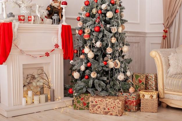 Sapin de noël décoré avec des cadeaux et une cheminée