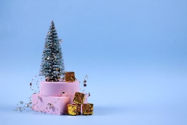 Sapin de noël décoré avec des coffrets cadeaux dorés et copyspace