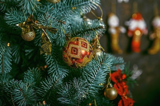 Sapin de noël décoré sur fond flou, mousseux et féerique. belles décorations de noël de couleur accrochées à l'arbre de noël avec des reflets brillants