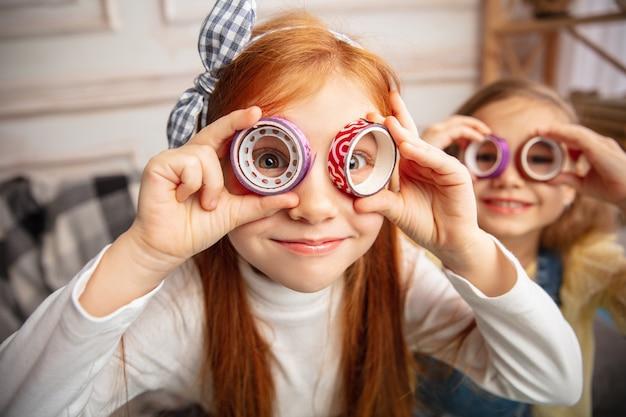 Sapin de noël. deux petits enfants, filles ensemble dans la créativité. des enfants heureux fabriquent des jouets faits à la main pour les jeux ou la célébration du nouvel an. petits modèles caucasiens. bonne enfance, préparation à la célébration.