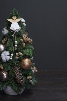Sapin de noël en épicéa nobilis frais, décoré d'ornements festifs et de pommes de pin