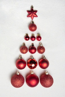 Le sapin de noël est fabriqué à partir de jouets de noël. des boules rouges et une étoile.