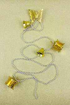 Sapin de noël fabriqué à partir de décorations d'hiver doré sur fond d'or avec copie vide
