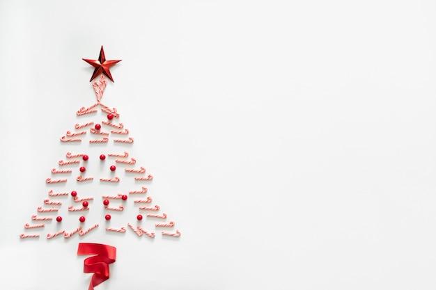 Sapin de noël fait de bonbons avec étoile rouge et ruban sur fond blanc
