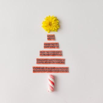Sapin de noël fait de bonbons à la guimauve, de fleurs et de bandes aigres.