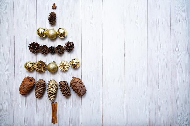 Sapin de noël fait de boules de noël dorées, cônes de cèdre et pommes de pin