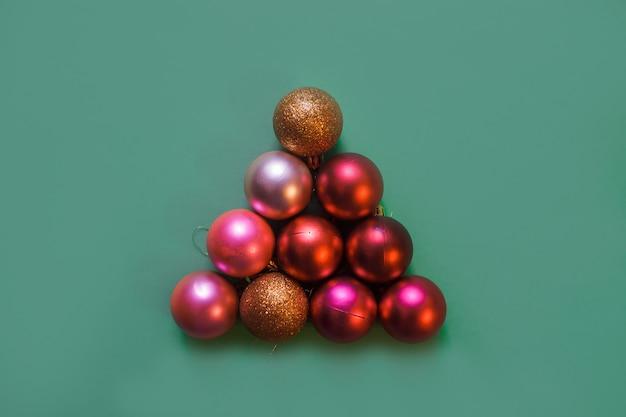 Sapin de noël fait de boules de noël dorées, rouges et roses sur fond vert, espace copie