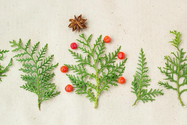 Sapin de noël fait de branches de thuya et de décorations étoiles d'anis et de framboise sur fond rustique.