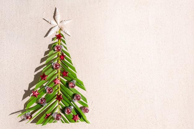 Sapin de noël fait de brunch de palme vert avec petites décorations festives rouges sur le sable