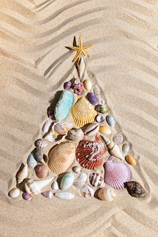Sapin de noël fait de coquillages et de coraux sur le sable de la plage, décoration festive