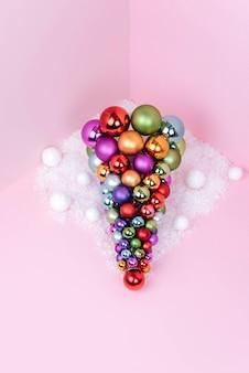 Sapin de noël fait de décoration de ballon sur fond rose.