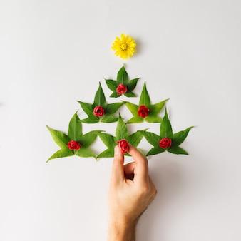 Sapin de noël fait de feuilles et de fleurs.